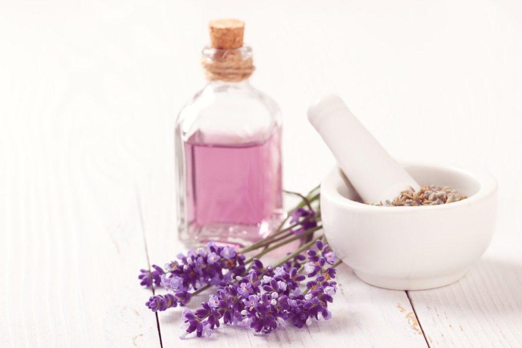 ラベンダーオイルの小瓶と乾燥ラベンダー、乳鉢の写真