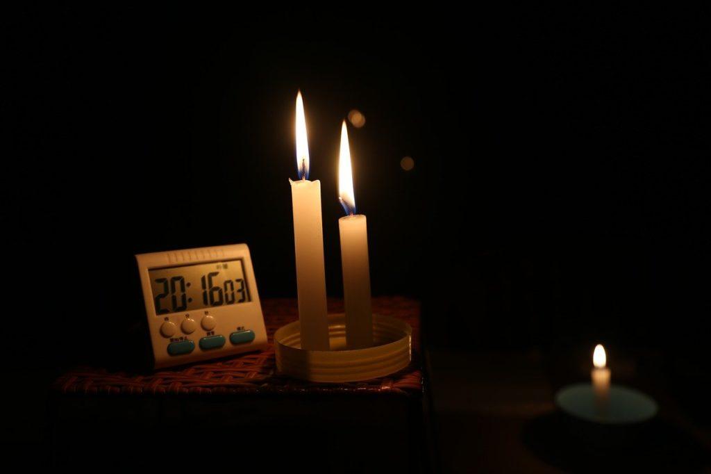 暗い部屋でろうそくを灯している画像