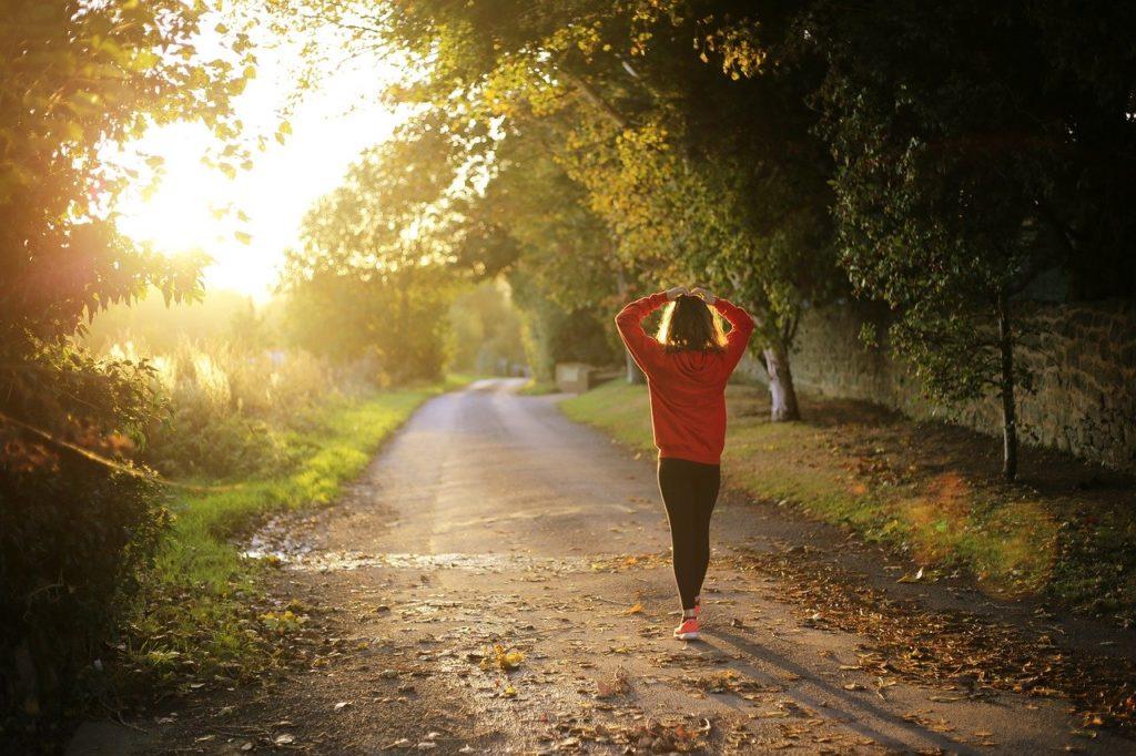 女性が朝日を浴びながら緑道を散歩している写真。