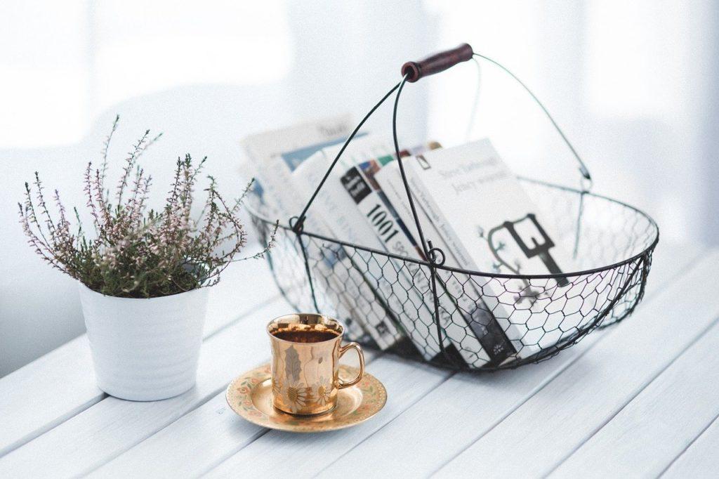 テーブルに置かれた数冊の本とマグカップ、植木鉢。