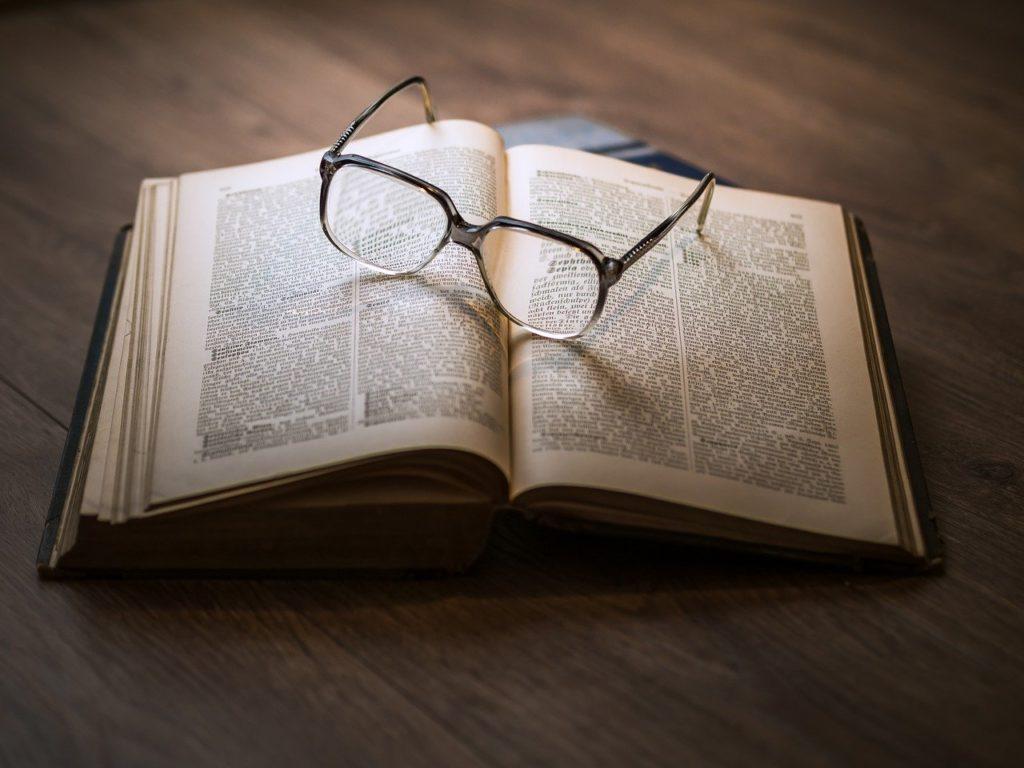 開いた本にメガネを置いた画像。