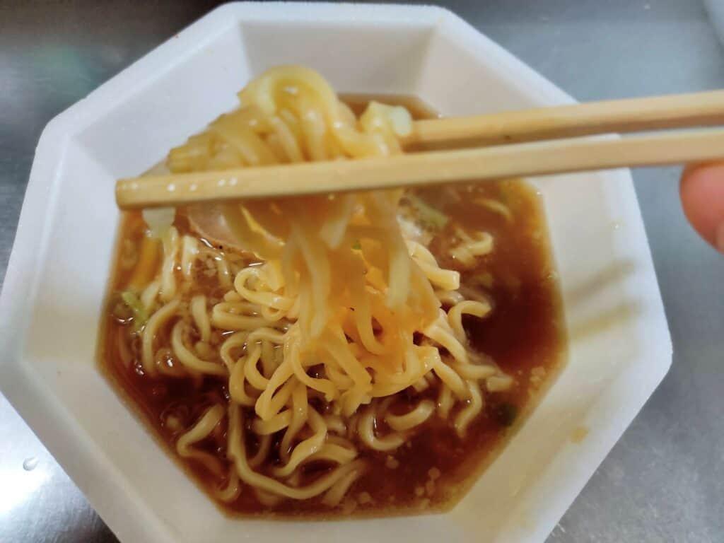 「日清豚ラ王 ヤサイ、アブラ、ニンニク」の麺を持ち上げた写真。