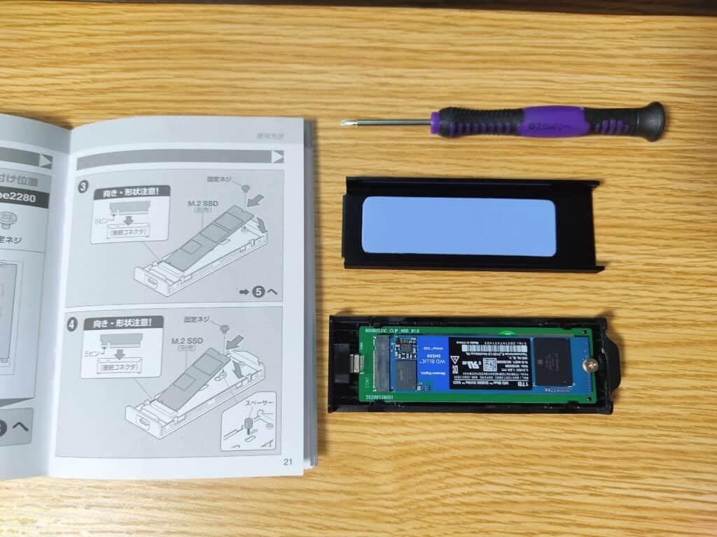 Western Digital SSD 1TB WD Blue SN550 PC M.2-2280 NVMeをセンチュリー「NVMe裸族のお立ち台プラス」専用ケースに取り付けるところ